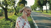 Woman speaking on phone while hitchhiking.