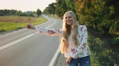 Young woman hitchhiking on countryside road. Dostupné videozáznamy