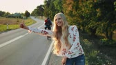 beira da estrada : Young lady hitchhiking on countryside road. Stock Footage