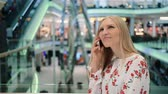 Young woman speaking on phone in mall. Dostupné videozáznamy