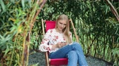 Young woman using smartphone in plant gazebo.
