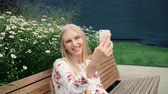 elektronika : Lovely young female using smartphone to make video call while sitting on bench on living roof of huge mall.