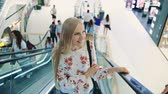 Young blonde woman riding on escalator. Amazed woman in shopping center. Young lady in elegant outfit riding on escalator on background of futuristic building in shopping center. Dostupné videozáznamy