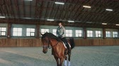 riding arena : Young woman sitting on horseback and riding on covered sandy arena having practice.