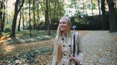 plavé vlasy : Beautiful young blonde girl walking in the park in autumn