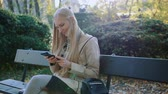 ławka : Young blonde girl uses a cell phone on a bench in the Park outdoors. Wideo