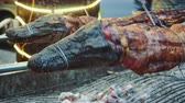 cooks : Grilled crocodile on the open fire at sea food restaurant, exotic meals in Viethnam, food of the asian cuisine, raw crocodile meat, exotic food Stock Footage