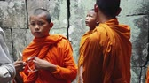 szerzetes : Young Buddhist Monks Walking In Temple In Saffron Robes and Looking Out Over Angkor Wat. Stock mozgókép