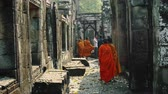 kamboçyalı : Young Buddhist Monks Walking In Temple In Saffron Robes and Looking Out Over Angkor Wat. Stok Video