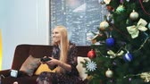 vr glasses : Side view of excited lady winning a video game on console on Christmas. She sits near the Christmas tree in the living room with skyscrapers in the background. There are also VR glasses headset on sofa. Stock Footage