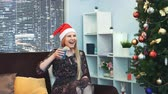 apito : Beautiful girl in Santa hat is waiting and emotionally celebrating the New Years coming with a glass of drink in her hands, blowing in party whistle. There are skyscrapers in the background. Stock Footage