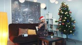 写真 : Attractive young lady making selfie in Santa hat and with drink in her hands. There are virtual reality goggles on sofa, a Christmas tree and skyscrapers in the background.