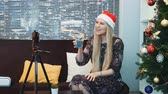帽子 : Side view of happy young lady in Santa hat recording video by smartphone on tripod. She has a drink in her hands and a Christmas tree on the right. There are also skyscrapers in the background. 動画素材