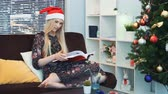 雑誌 : Middle close up of smart woman in Santa hat attentively reading book sitting on sofa at home. In the background there are skyscrapers. On the right there is a Christmas tree. 動画素材