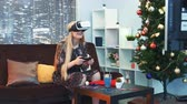 telewizor : Joyful woman playing a game with joystick in virtual reality glasses in front of TV on Christmas. There are skyscrapers in the background.Future technology concept.