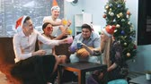приятель : Happy New Years celebration in cheerful company in Santa hats nd party masks making toasts to each other sitting near the Christmas tree