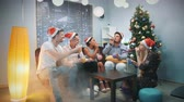 Multi-ethnic company in Santa hats blowing party whistle and making cheers in smoke. They sit on sofa near the xmas tree with skyscrapers in the background.
