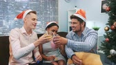ünnepségek : Close up of two boys and a girl in Santa hats making cheers and blowing party whistles. They have fun celebrating holidays together. Elements of this image furnished by NASA.
