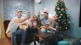 呼び出し : Cheerful friends in Santa hats making video call by smartphone on Christmas party while blowing party whistle, making cheers and having fun together.