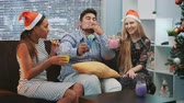 Beautiful young people in Santa hats making cheers and blowing party whistle. They sittng on sofa, smiling and drinking. Friends happiness concept