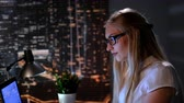 a view : Close-up of young female scientist searching books in Internet late at night. In the background there are skyscrapers. Stock Footage