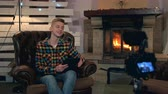 videocamara : Home video shooting: teenage boy speaking something to camera with tablet in his hands. He sitting in comfortable leather armchair near the fireplace