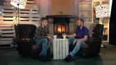 zoon : Dad and son talking over a cup of warm drink at home sitting in cozy place at home with fireplace in the background