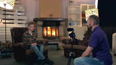 zoon : Father shoots his son on camera for his personal internet blog. The boy sitting with tablet near the fireplace Stockvideo