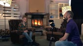 zoon : Dad helping his son to become a TV presenter by shooting the boy on home video camera. They sitting in the living room with fireplace in the background. Stockvideo