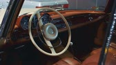 tachimetro : Vintage car interior: shiny brown dashboard, leather sits and milk steering wheel. Close-up shot Filmati Stock