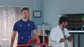 estresse : Mixed race doctor performing stress test while the athlete walking on treadmill. Computer supervises whole test process