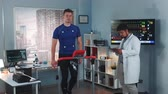 심장학 : Scientific sports laboratory: doctor coming to monitor athletes stress testing. The displays in lab showing EKG data.