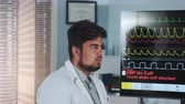 診断 : Close-up of mixed race doctor learning EKG data showed on big display in modern sports lab. 動画素材