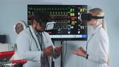sports : Mixed race doctors in VR glasses discussing about something in modern sports lab with EKG data on display in the background.