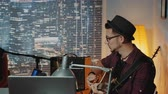輪郭 : Profile view of handsome hipster singing into microphone and playing the guitar in home recording studio. There are skyscrapers in the background. 動画素材