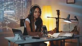 çapa : Multiracial female journalist doing online interview on the computer in home recording studio in the evening. Woman is in headphone.