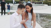 sedět : African young woman is upset because of her boyfriend looking in the smartphone all the time. She asking him to stop doing that on their date. Dostupné videozáznamy