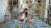 мама : Baby girl and mom play with plasticine in the art studio. Educational game