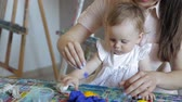 мама : Kid girl and mom play with plasticine at home
