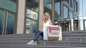 shopaholic : Young girl sitting on the steps with shopping bags, talking on the phone. Stock Footage