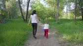 Mom and daughter walking in the park Archivo de Video