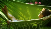 educação : Young woman lying on hammock on backyard.