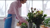 декоратор : Florist at work: young woman making modern bouquet of different flowers