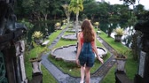 zadnice : A young girl descends the stairs in ancient beautiful park, in Bali