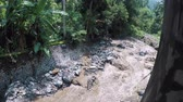 storm drain : A dirty river descends from the mountains in the jungle after a rain
