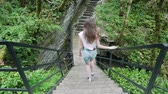 descend : View from the back: the girl descends the stairs in the rain forest