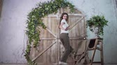звук : A tall model actively poses and dances with a smile against the background of a wooden photozone