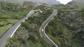 enrolamento : Aerial view. Narrow serpentine, in which it is difficult to drive cars towards each other. The road along the mountain range, different cars, a tropical climate.