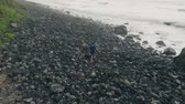 oceano atlântico : A man walks alone along a black beach made up of large stones. The hard way to the Atlantic Ocean. Tenerife, Canary Islands, Spain. AERIAL Vídeos