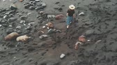 oceano atlântico : Perfect aerial footage from the island of Tenerife - a young, stylishly dressed girl in a hat, walking along a black beach of volcanic sand. Cinematic top view. Canary Islands, Spain